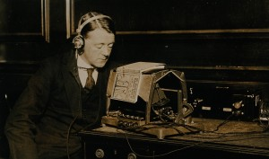 Photograph from ca. 1921 of a man listening to an Optophone, a mechanical reading device for blind people.